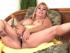 Curvaceous, blonde mature, Joclyn Stone is using a glass dildo to drill her hairy pussy