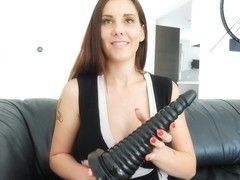 Lilian is rubbing a big, black dildo with her massive tits before drilling her pussy with it