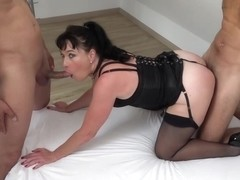 Mature woman, Berenice is riding one rock hard cock while trying to suck another one