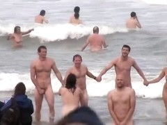 Hundreds of nudist people running into the sea naked